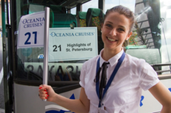 Tour guide Nina Kazarina in front of an Oceania Cruise tour bus in St. Petersburg, Russia